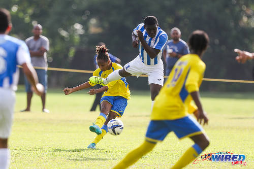 "Photo: Shiva Boys HV star Tyrel ""Pappy"" Emmanuel (centre) drives towards goal while St Mary's College midfielder Nathan Harte (airborne) makes a vain attempt at a block. (Courtesy Chevaughn Christopher/Wired868)"